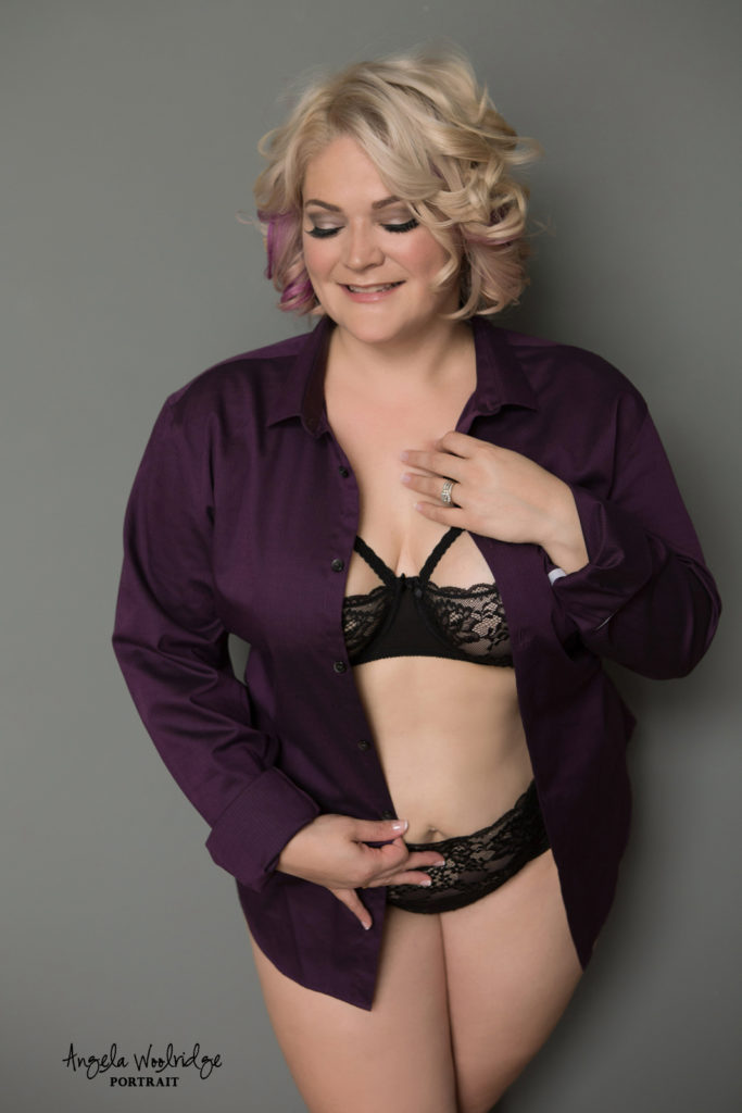 Woman in her husband's shirt in boudoir photography session