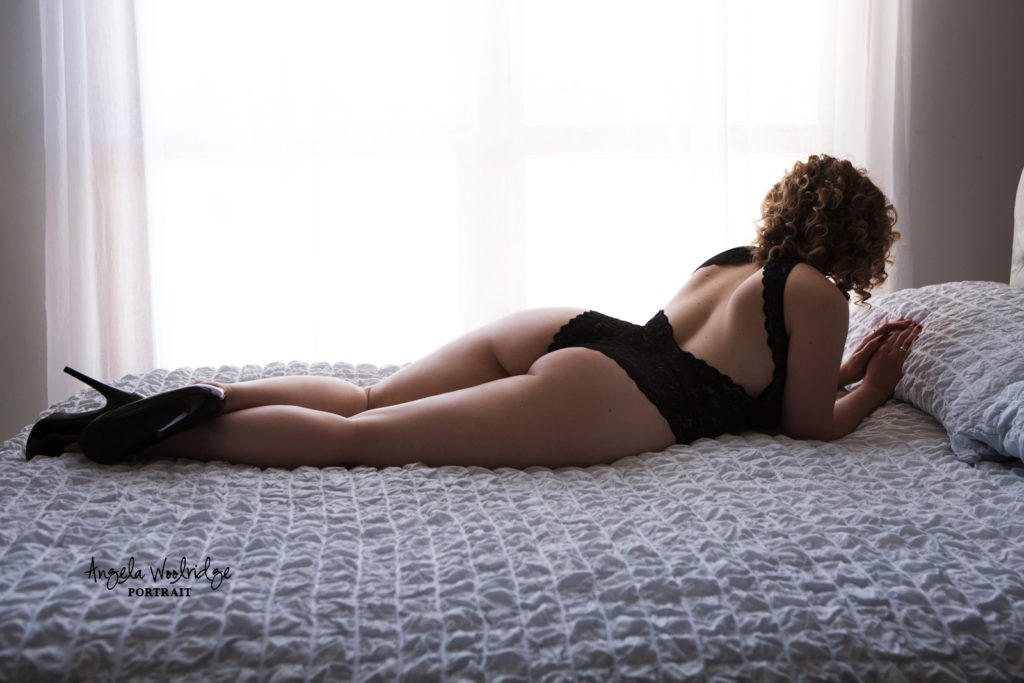 Sexy boudoir photo of woman relaxing on bed