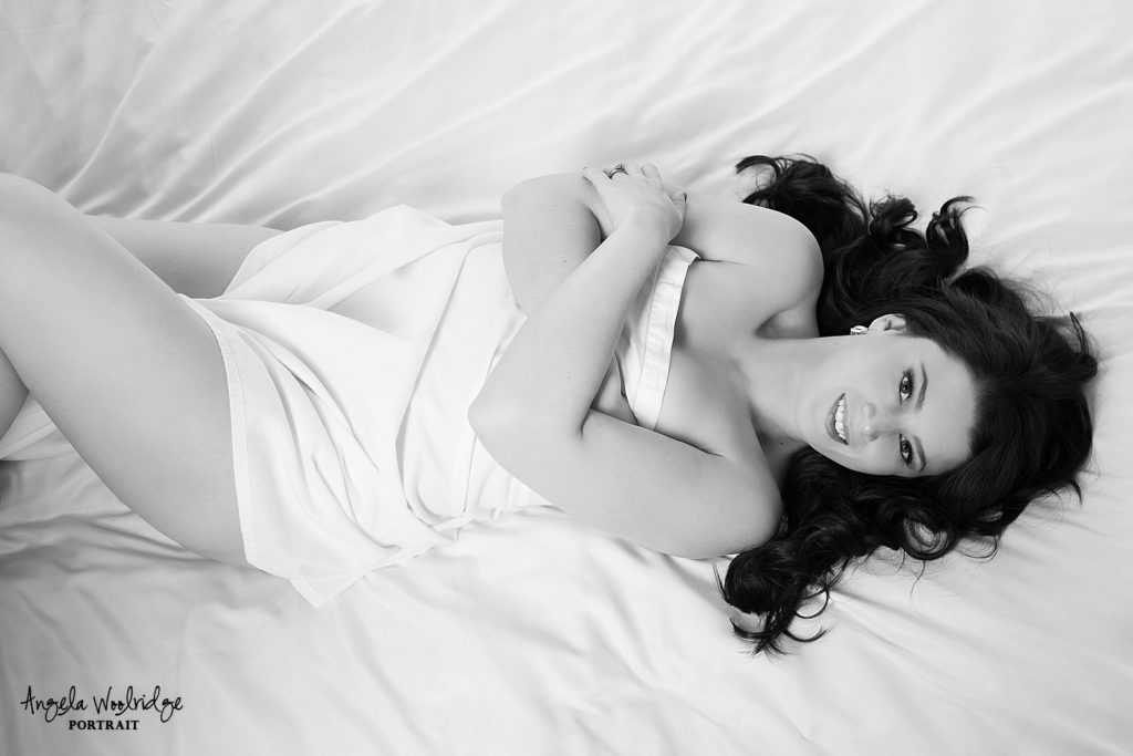 Black and white of lady in white sheet boudoir session.